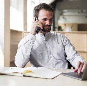 hombre joven que habla telefono celular mientras trabaja computadora portatil 23 2148187181@3x